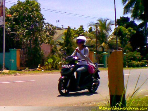 Perempuan riding, ponsel, tas, jaket