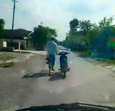 Pengendara sepeda nuntun motor